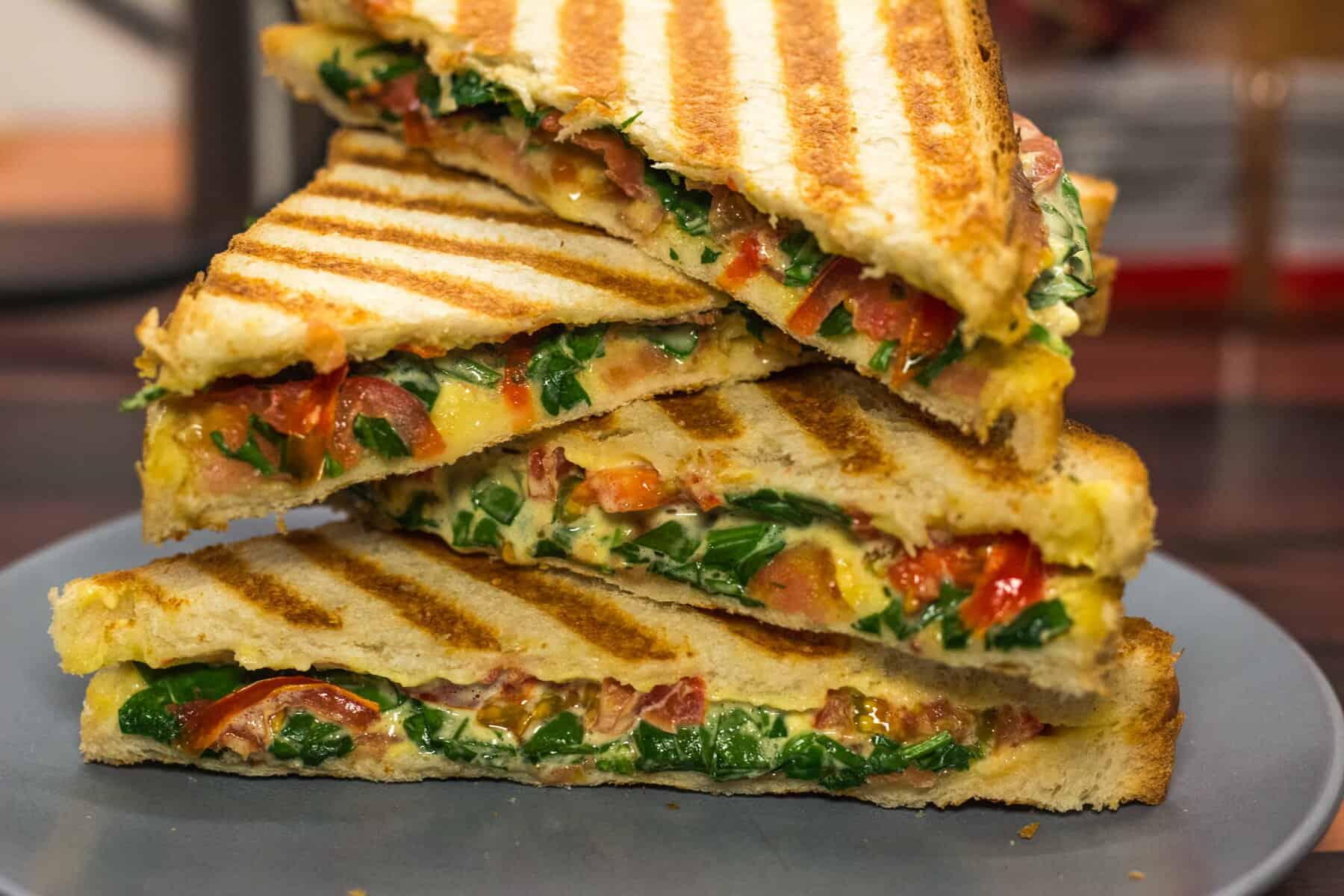 Panini-Sandwich mit Sauce Hollandaise, Bacon, Spinat und Tomate
